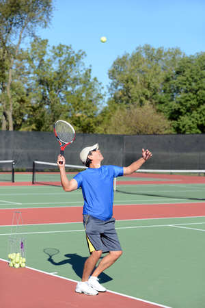 Mature Hispanic tennis player serving ball on court photo