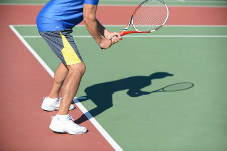 Tennis Player holding racket casting shadow on court Banco de Imagens