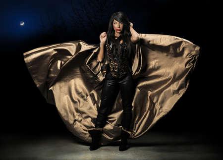 暗い背景上マントを飛んでいると女性の吸血鬼 写真素材