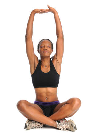 African American woman stretching in sitting position isolated over white background photo