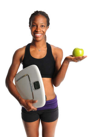African American woman holding apple and scale isolated over white background photo