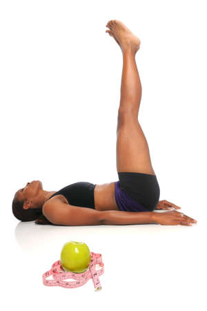 African American woman stretching with apple and measuring tape in foreground - with selective focus on front Stock Photo