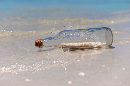 Message in a bottle with waves crashing on shore Stock Photo