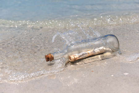 castaway: Waves splashing on message in a bottle laying on shore Stock Photo
