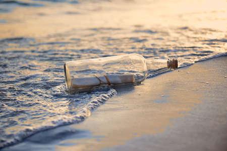Boodschap in een fles op het strand tijdens zonsondergang Stockfoto
