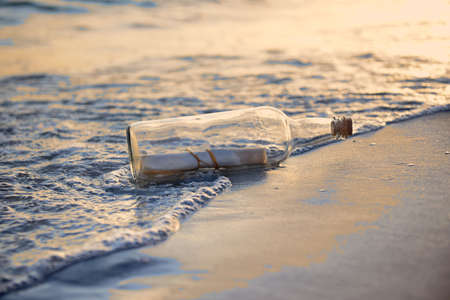 Message in a bottle on beach during sunset photo