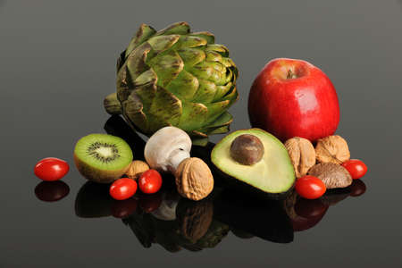 Assortment of fresh fruits and vegetables on reflective table photo