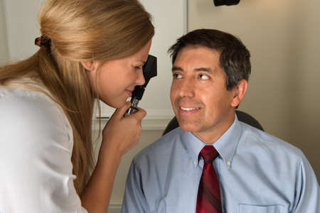 ophthalmologist: Female eye doctor examining Hispanic patient in office