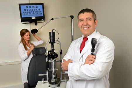 Hispanic eye doctor and female assistant in examination room