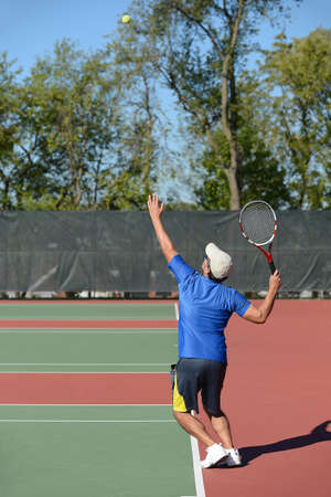 Mature man playing tennis on court photo