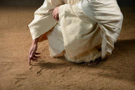 Jezus schrijft in het zand met een vinger Stockfoto