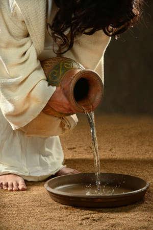 Jesus gießt Wasser in den Behälter über dunklen Hintergrund Standard-Bild