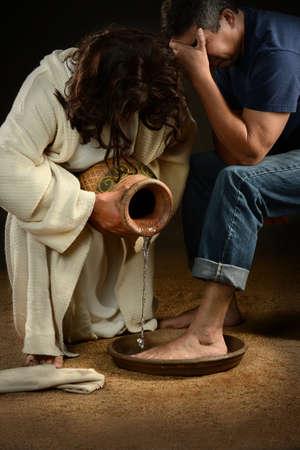 lavandose las manos: Jesús lavando los pies de los pantalones vaqueros hombre que llevaba Foto de archivo