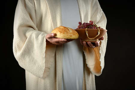 Jesus hands holding bread and grapes, symbols of communion photo