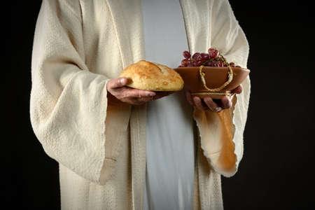 Les mains de J�sus tenant le pain et les raisins, les symboles de communion Banque d'images - 16707707