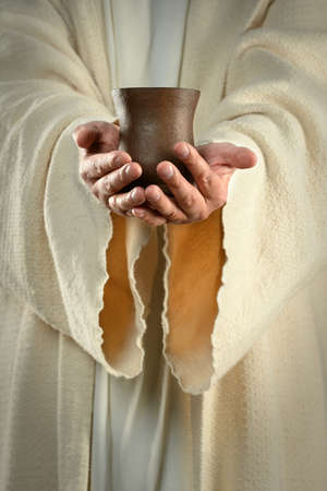 Hands of Jesus holding cup of wine photo
