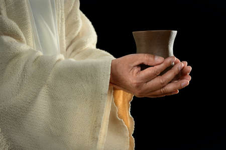 bread and wine: Jesus hands holding cup over dark background