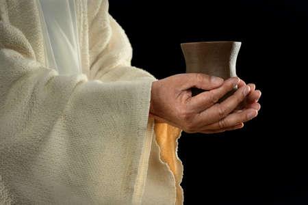 Jesus hands holding cup over dark background