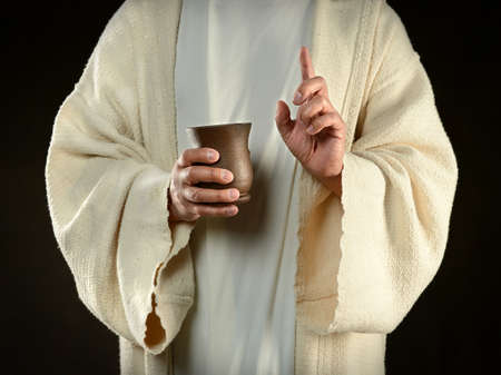 Jesus hands holding cup of wine isolated over dark background Banque d'images