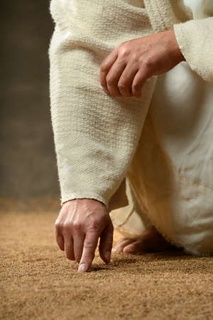 jesus hands: Jesus finger writing in the sand in close up view Stock Photo