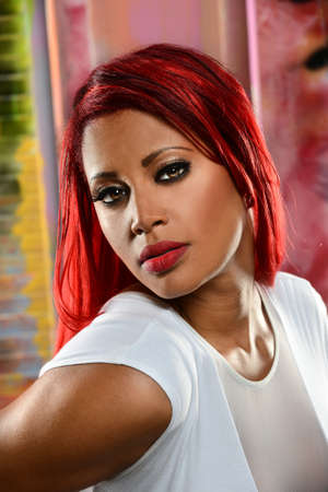 Young African American woman with red hair over colorful background photo