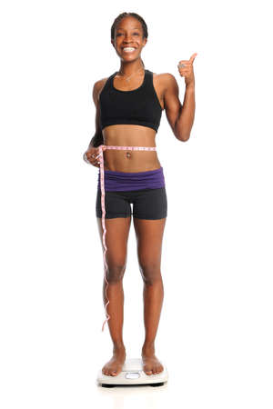 African American woman on scale with measuring tape around waist over white background photo