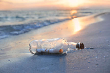 Message in a bottle resting on shore during sunset Stock Photo