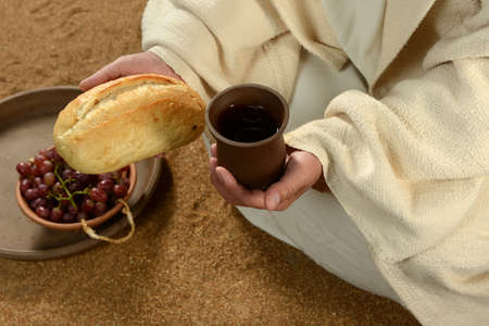Jesus hands holding bread and wine with tray of grapes in background Stock Photo