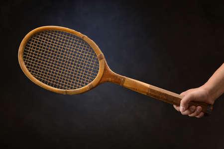 tennis racket: Mans hand holding vintage tennis racket over dark background
