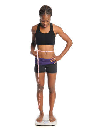 African American woman standing on scale with measuring tape around waist