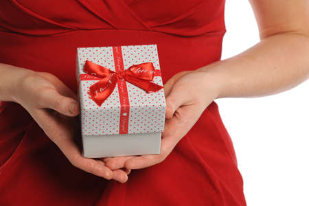 adult valentine: Womans hands holding gift box with red ribbon isolated over white background Stock Photo
