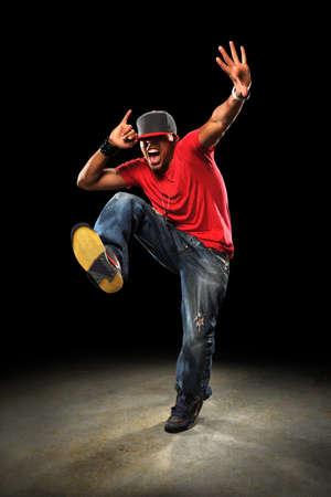 bolantes: Bailar?n de rap afroamericano realizando sobre fondo oscuro con spotlight