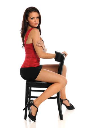 Portrait der schönen jungen Frau auf schwarzem Stuhl über weißem Hintergrund sitzt