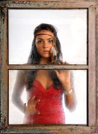 Portrait of beautiful woman with feather adornment looking through window photo