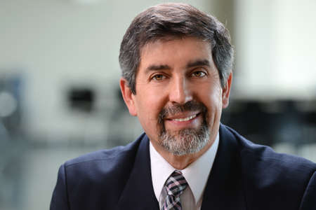 Portrait of Hispanic businessman smiling indoors
