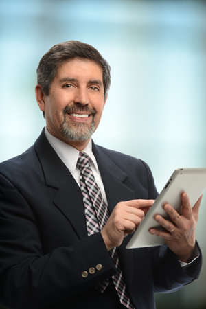 older men: Portrait of mature Hispanic businessman using electronic tablet indoors Stock Photo