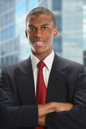 Portrait of African American businessman smiling with business district in background