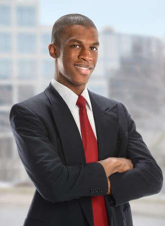Portrait of African American Geschäftsmann mit gekreuzten Armen mit Bürogebäude im Hintergrund
