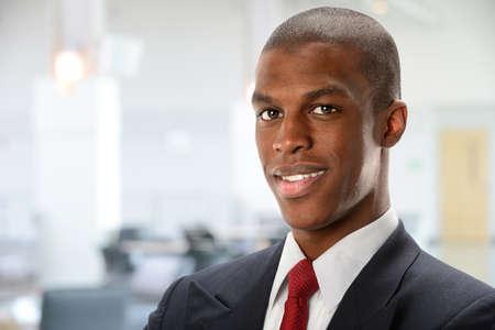 black business man: Portrait de jeune homme d'affaires afro-am�ricaine avec immeuble de bureaux en arri�re-plan