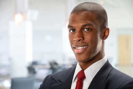 Portrait of young African American businessman with office building in background