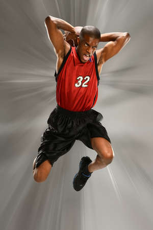 African American basketball player slam dunking the ball over abstract background