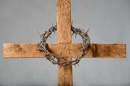 Wooden cross and crown of thorns over neutral background photo