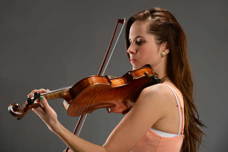 violins: Portrait of young woman playing violin over gray background