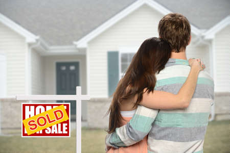 house property: Young couple embracing in front of house with sold sign