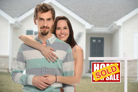 Young couple embracing in front of house with sold sign behind them photo