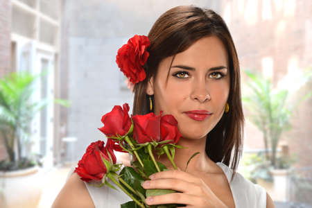 Portrait of beautiful Hispanic woman holding red roses  photo