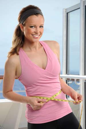 woman measuring waist: Beautiful young woman measuring waist in outdoor spa