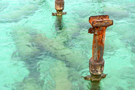 Rusted metal posts from pier in clear Caribbean waters Reklamní fotografie