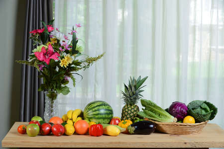 Assortment of fresh fruits and vegetables on wooden table by window photo