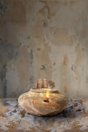 israelite: Ancient Middle Eastern oil lamp on clay surface